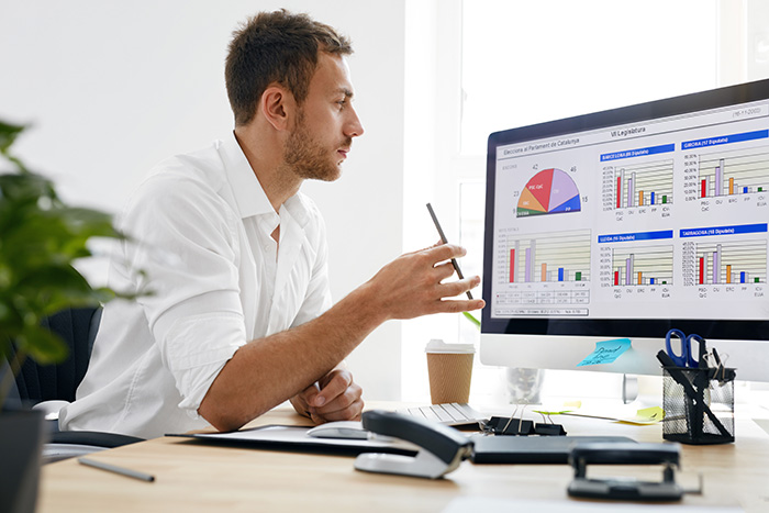 Business executive reading business intelligence report on computer