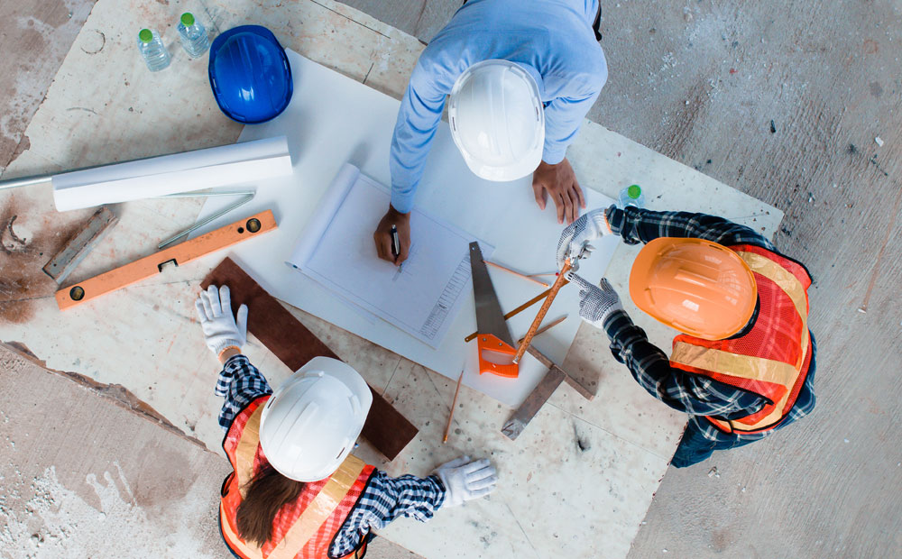 Construction workers creating building plans using data analytics